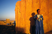 A boy at dawn with his loaf of bread, Chinguetti, Mauritania. Chinguetti was a 'ksar' or medieval trading centre that was founded in the 6th century and for centuries the city was a principal gathering place for pilgrims of the Maghrib to gather on the way to Mecca. It is known for it's ancient libraries full of priceless books and Korans and is said to be the seventh holiest city in Islam