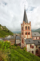 View of St Peter Church and colorful Bacharach housing, with a vineyards, cloudy sky and mountains in the background, Bacharach, Germany.