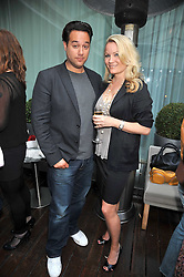 RICHARD RAYMOND and GEORGIA BLAKEY at the Total Concierge launch party held in the stylish Courtyard Garden at Sanderson, Berners Street, London on 26th May 2009.