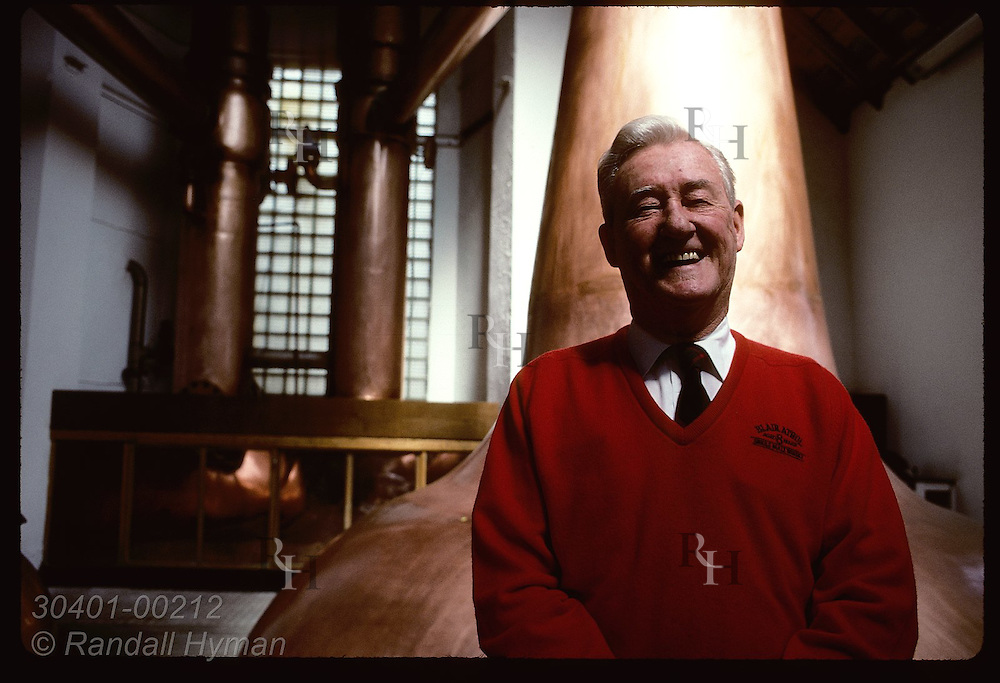 Tour guide Peter Monachan laughs as he poses in still room of Blair Athol Distillery;Pitlochry Scotland