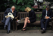 A lady sharing a City of London park bench with two other workers, reads a copy of a newspaper during her lunch hour, on 22nd June 1993, in London, England.