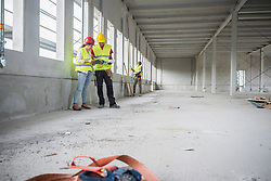 Architect with construction workers at building site, Munich, Bavaria, Germany