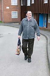 Older man walking down the road on his way to the shops,