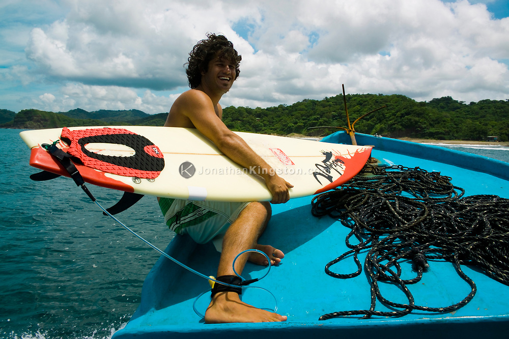 A surfer smiles for the camera before he jumps off the boat to catch a wave in to Maderas Beach, located near San Juan Del Sur, Nicaragua. Once a little known and sleepy vacation spot, San Juan Del Sur has become increasingly popular for its beautiful beaches, small fishing town feel, and respected surf break.