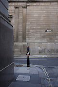 A visual pun of a lunchtime pedestrian on the corner of Lothbury and Tokenhouse Yard, two narrow and historic streets with the high walls of the Bank of England in the background - in the City of London, the capital's financial district. The area was populated with coppersmiths in the Middle Ages before later becoming home to a number of merchants and bankers. Lothbury borders the Bank of England on the building's northern side. Tokenhouse St dates from Charles I and was where farthing tokens were coined. The City of London is the capital's historic centre first occupied by the Romans then expanded during following centuries until today, it has a resident population of under 10,000 but a daily working population of 311,000.