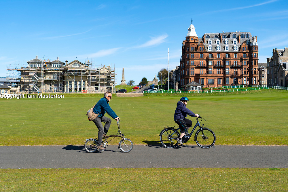 St Andrews, Scotland, UK. 4 May 2020.  The famous Old Course at St Andrews is closed due to the coronavirus lockdown. Locals are making the most of the closed golf course by using it as a park for they daily exercise. Couple cycle on path crossing the first and eighteen fairways.   Iain Masterton/Alamy Live News