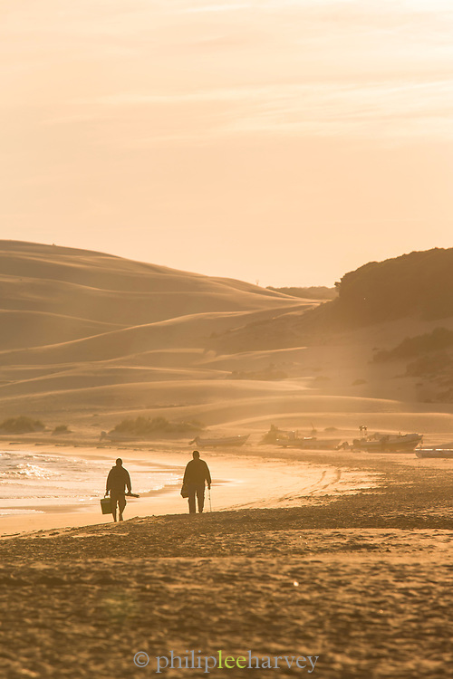 Two people walking on beach at sunrise with hills in background, Cadiz, Andalusia, Spain