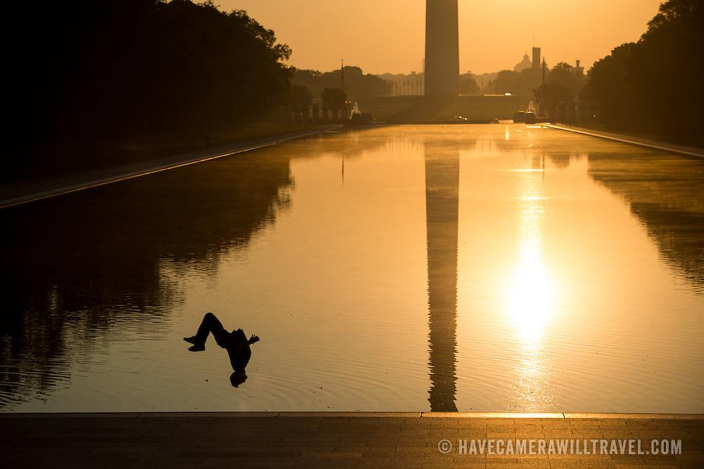 WASHINGTON, DC--A man does backflips next to the Reflecting Pool at sunrise.