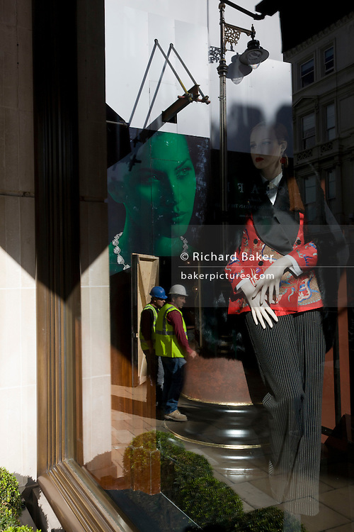 Construction workers reflected in a Bond Street shop window along with fashion mannequin and model's face.