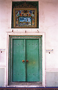 The double leaf door which connects the outer from the inner prayer galleries of the Id Kah Mosque, Kashgar city. It  began life in its present form in 1798, before this time it had been a place of worship during the Ming dynasty (1368-1644), built on a smaller mosque dating back to the 15th century. It is the largest mosque in western China with the purest Uighur ( a Muslim minority of Turkic origin) architecture, its colours reflecting the arid environment it inhabits. Inside it contains a large octogonal shaped pavilion and internal courtyard which can allow up to 7000 worshipers in at any one time. It is the symbol of Uighur cultural and religious presence  for the whole of the central Chinese and neighbouring Asian countries, such as Kyrgyzstan, Tajikistan, Uzbekistan, Turkestan, Afghanistan, and Pakistan.