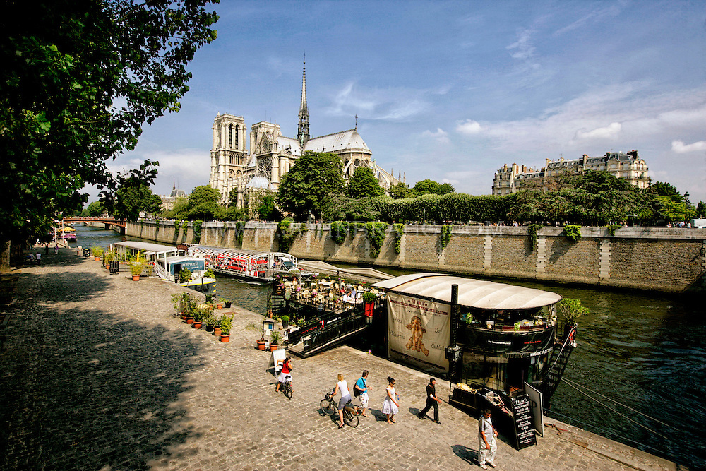 Restaurants and Riverboats  along the Seine River, Notre Dame Cathedral in the background, Paris, France.