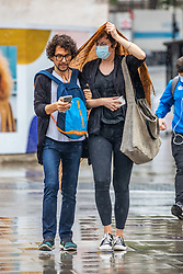 © Licensed to London News Pictures. 19/08/2020. London, UK. Members of the public get caught in heavy rain with gusty winds in Westminster today as weather forecasters predict a warmer and sunnier week ahead with highs of 24c . Photo credit: Alex Lentati/LNP