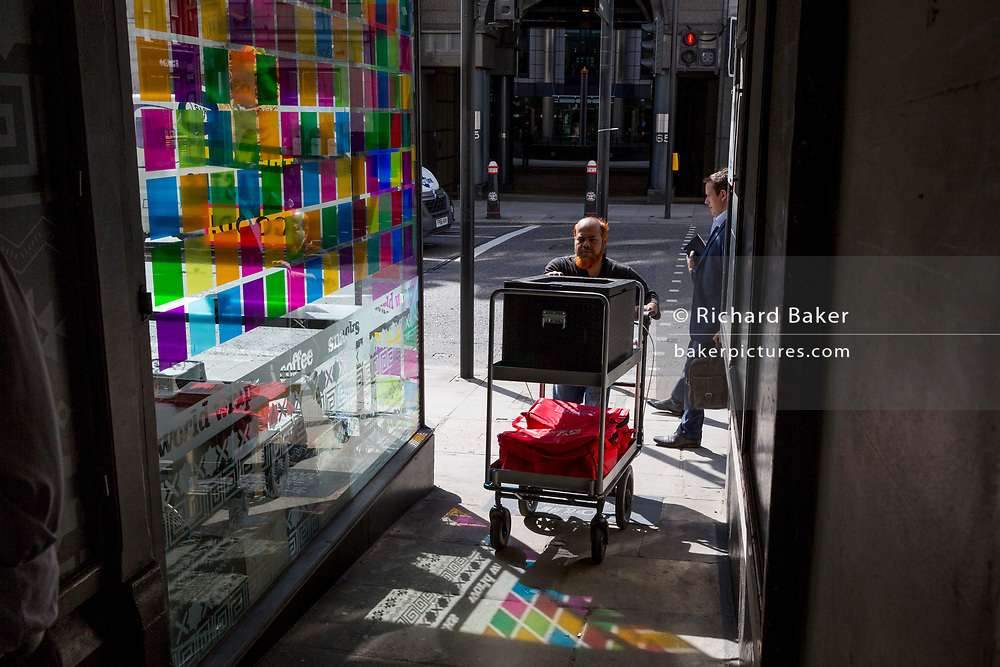 A delivery man pushes his trolley through coloured light from a corner cafe reflected on the pavement on Fleet Street in the City of London, the capital's financial district (aka the Square Mile), on 22nd August 2019, in London, England.