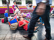 11 APRIL 2015 - BANGKOK, THAILAND:  People sleep on a bench on the platforms while passengers walk past them at Hua Lamphong train station in Bangkok. More than 130,000 passengers streamed through Bangkok's main train station Friday ahead of Songkran, Thailand's traditional new year celebration. Songkran will be celebrated April 13-15 but people started streaming out of Bangkok on April 10 to go back to their home provinces.   PHOTO BY JACK KURTZ