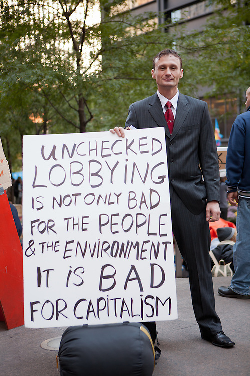 "A man in a gray business suit with a large sign reading ""Unchecked lobbying is not only bad for the people & the environment it is bad for captialism."""