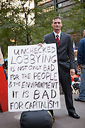 """A man in a gray business suit with a large sign reading """"Unchecked lobbying is not only bad for the people & the environment it is bad for captialism."""""""