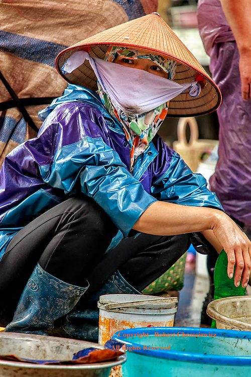 A female fish monger looks up from her work, peeking out from behind an oriental hat and handkerchief that otherwise covers her face, at the morning market in Ninh Binh Vietnam.