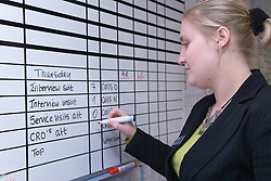 Polish office worker writing on whiteboard to monitor her progress at work,