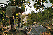 A woman washes her clothes at the only natural spring in the mountains above Carrefour, Haiti.  The spring is the only natural source on the mountain and people walk for hours up the mountain to collect water, bathe and wash their clothes.  Once done they will fill buckets with water and carry it back to their homes.