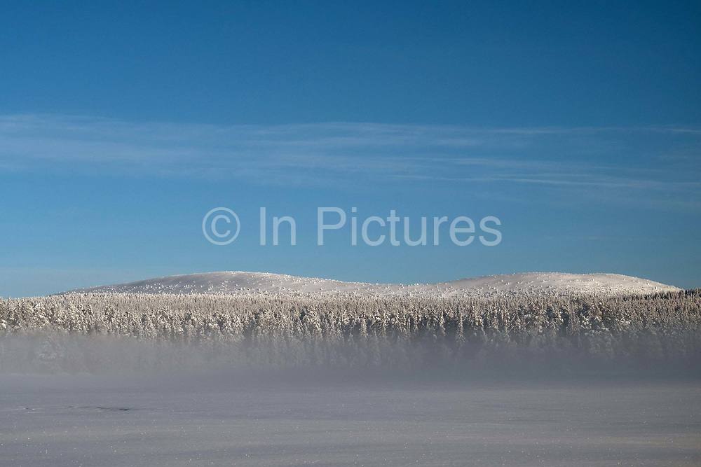Mist rising over the snowy Winter landscape of the forest and fells on the edge of Jeresjarvi lake on 17th February 2020 in Finnish Lapland.  Jeresjarvi is on the edge of Pallas-Yllastunturi National Park, the third largest national park in Finland and is located in the Lapland region. The natural features and landscape of the fells have always enchanted hikers and the area offers magnificent fells and seemingly endless woodlands.