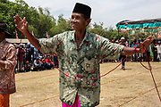 A farmer dances his sapi (cow) down the field in competition for the most beautiful cows of the region at the annual Festival Sapi Sono'. Participants come from all four regions of Madura (Bangkalan, Sampang, Pamekasan, and Sumenep) and competitions began in the 1950s.  Racing the cows the following day is a ritual that has been around since the 14th century. Stadion R. Soenarto Hadiwidjojo in Pamekasan, Madura, Indonesia.