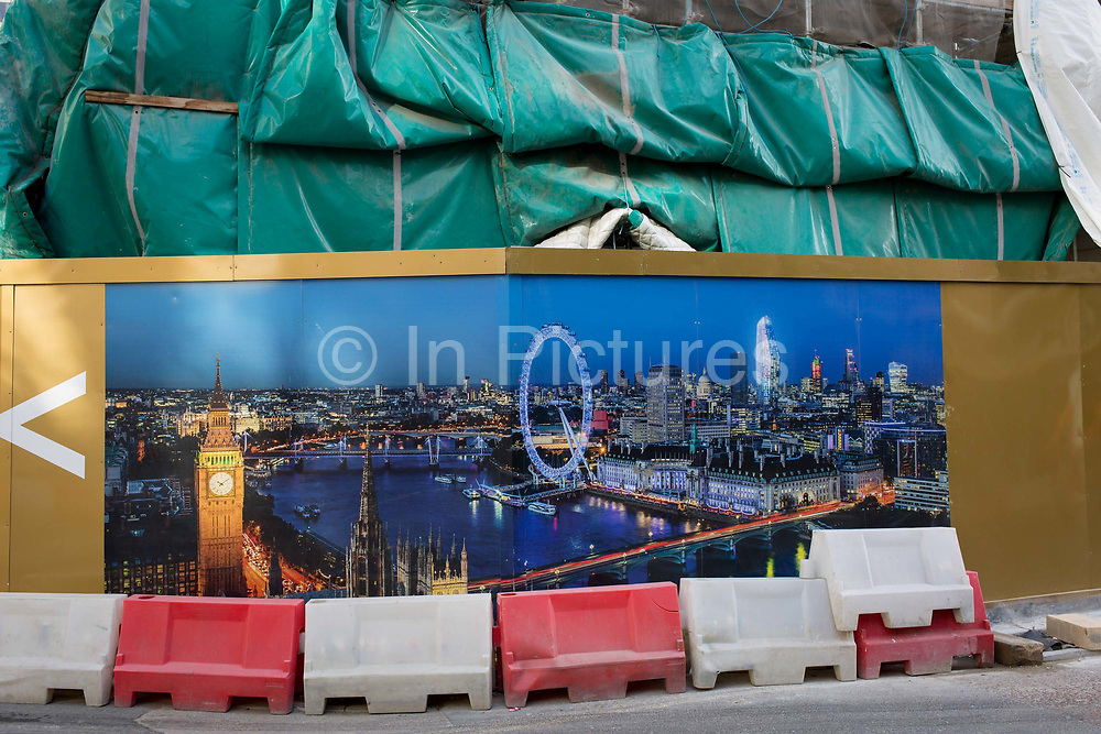 Construction hoarding showing the capitals landmarks and the River Thames, plus an overhead tarpaulin sheeting at the St George tower, on 2nd March 2017, at One Blackfriars, in the London borough of Southwark, England.