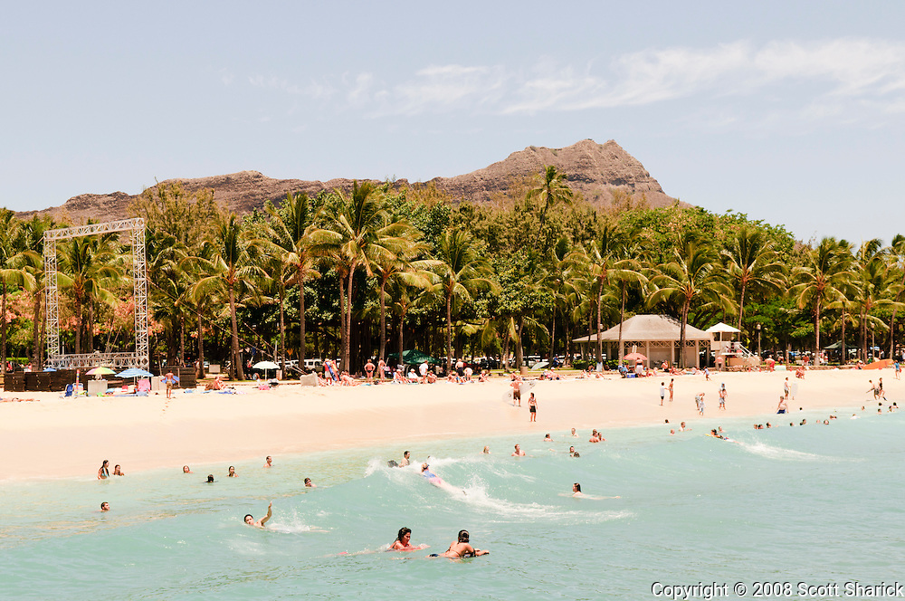 In this picture of Waikiki you can see Diamond Head Crater peaking over the top of the palm trees along the white sand beach.