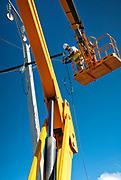 photographie couleur d'un travailleur dans une nacelle travaillant sur l'installation des réseaux électriques pendant la construction du complexe pyrométalurgique de Vavouto en Province Nord, Nouvelle Calédonie.