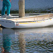 Person walking past a dinghy tied to the dock at the Ellsworth Harbor public boat landing.