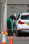 NHS staff see a patient who remains in their car at a drive-through Primary Care Clinical Assessment Centre where potentially infectious and symptomatic Coronavirus patients can be assessed and treated by a doctor or a nurse, in a safe site, on the 16th of April 2020 in Dover, United Kingdom. This is not a COVID-19 testing facility, all patients will only be clinically assessed on site as there is no community testing currently available. All patients have been referred to this centre by NHS 111 or their GP. ((photo by Andy Aitchison)