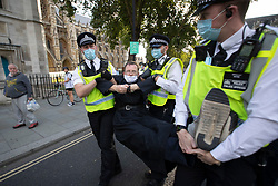 © Licensed to London News Pictures. 01/09/2020. London, UK. Police remove an Extinction Rebellion protester from a demonstration in Parliament Square. The environmental activist group intend to peacefully blockade the Houses of Parliament until Parliament agrees to debate their three demands.  Photo credit: George Cracknell Wright/LNP