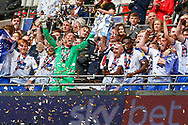PROMOTED Tranmere Rovers defender Steve McNulty (5) and Tranmere Rovers goalkeeper Scott Davies (1) lift the trophy as teammates celebrates after winning the EFL Sky Bet League 2 Play Off Final match between Newport County and Tranmere Rovers at Wembley Stadium, London, England on 25 May 2019.