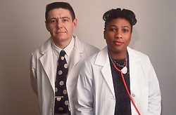 Portrait of male and female hospital doctors wearing white coats standing together,