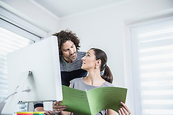 Businesswoman showing file to his Colleague in an office, Munich, Bavaria, Germany