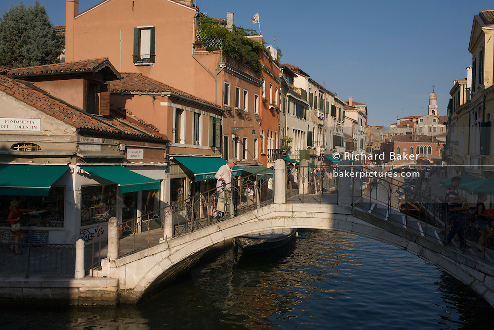 Tourists on the Fondamenta Minotto and on the bridge over the Rio dei Tolentini Canal in Dorsoduro, a district of Venice, Italy.