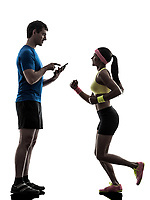 one woman exercising jogging with man coach using digital tablet in silhouette on white background