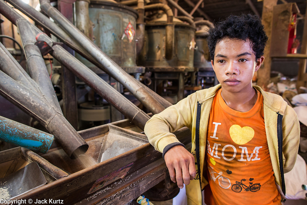 "29 JUNE 2013 - BATTAMBANG, CAMBODIA:   A worker in a rice mill at his work station. The mill is next to the tracks that carry the ""bamboo trains."" The bamboo train, called a norry (nori) in Khmer is a 3m-long wood frame, covered lengthwise with slats made of ultra-light bamboo, that rests on two barbell-like bogies, the aft one connected by fan belts to a 6HP gasoline engine. The train runs on tracks originally laid by the French when Cambodia was a French colony. Years of war and neglect have made the tracks unsafe for regular trains.  Cambodians put 10 or 15 people on each one or up to three tonnes of rice and supplies. They cruise at about 15km/h. The Bamboo Train is very popular with tourists and now most of the trains around Battambang will only take tourists, who will pay a lot more than Cambodians can, to ride the train.       PHOTO BY JACK KURTZ"