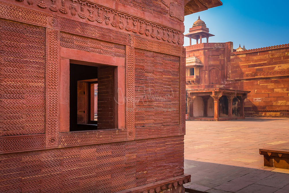 """Fatehpur Sikri is a city and a municipal board in Agra district in the state of Uttar Pradesh, India. The city was founded in 1569 by the Mughal emperor Akbar, and served as the capital of the Mughal Empire from 1571 to 1585. After his military victories over Chittor and Ranthambore, Akbar decided to shift his capital from Agra to a new location 23 miles W.S.W on the Sikri ridge, to honor the Sufi saint Salim Chishti. Here he commenced the construction of a planned walled city which took the next fifteen years in planning and construction of a series of royal palaces, harem, courts, a mosque, private quarters and other utility buildings. He named the city, Fatehabad, with Fateh, a word of Arabic origin in Persian, meaning """"victorious."""" it was later called Fatehpur Sikri. It is at Fatehpur Sikri that the legends of Akbar and his famed courtiers, the nine jewels or Navaratnas, were born. Fatehpur Sikri is one of the best preserved collections of Mughal architecture in India."""