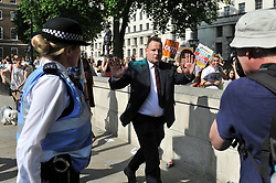 @ Licensed to London News Pictures 17/06/2017. Central London, UK. A suited member of the public is showered in luminous glitter during the No Coalition of Chaos with the DUP protest outside Downing Street today in Central London.Photo credit: Guilhem Baker/LNP