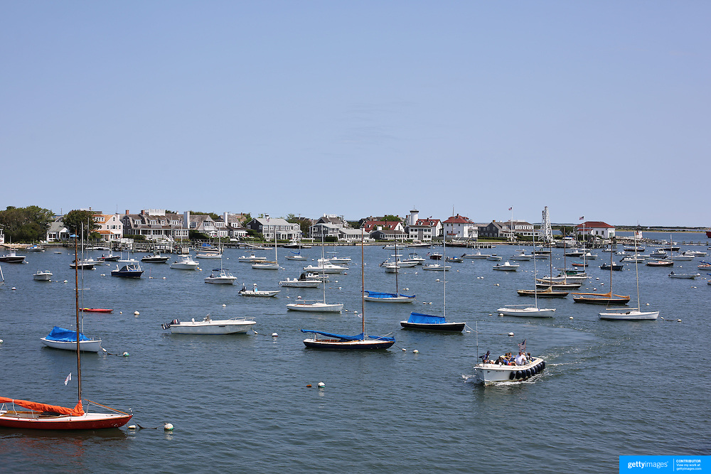 A fishing trip returns to the harbor passing sail boats moored in Nantucket Harbor, Nantucket Island, Massachusetts, USA. Photo Tim Clayton