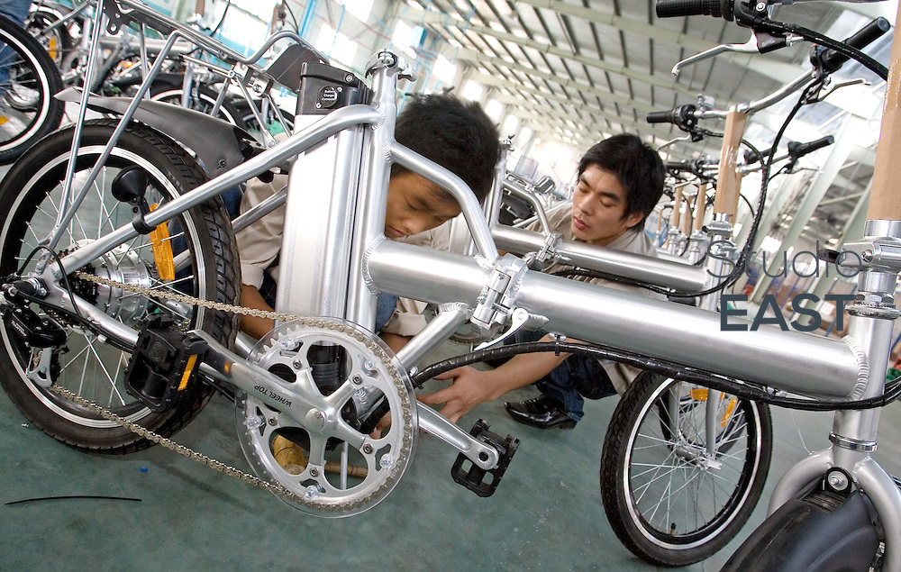 ZHEJIANG PROVINCE, CHINA - September 17: Workers work on electric bicycles in Repow electric vehicles factory on September 17, 2007 in Jinhua, Zhejiang province, China. (Photo by Lucas Schifres/Getty Images)