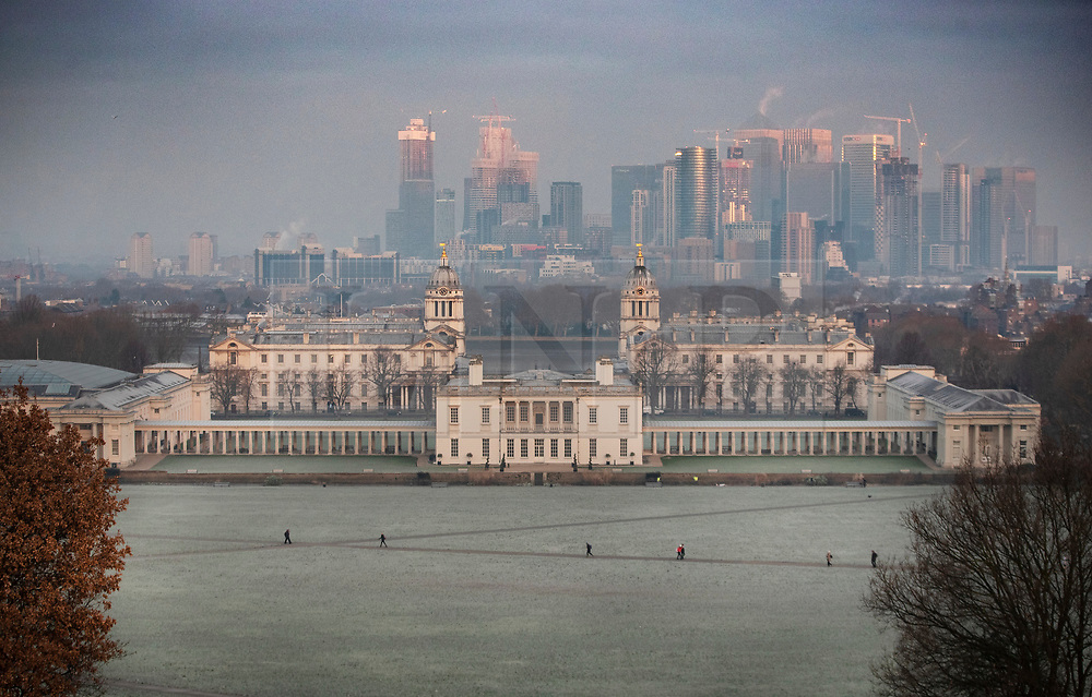 © Licensed to London News Pictures. 21/01/2019. London, UK. People walk across frozen ground in Greenwich Park as the morning sun reaches the top of the Docklands sky scrapers. Photo credit: Peter Macdiarmid/LNP