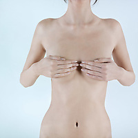 studio shot detail picture of a breast naked hiding by hands