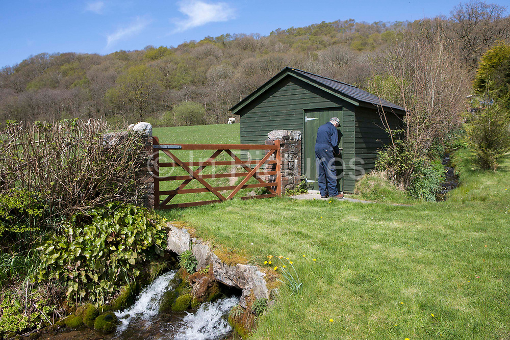 Welsh sheep farmer Howell Williams and his sheep dog Ben accessing the generator room to the 15kW micro hydro power plant producing electricity at Abercrave Farm on the Brecon Beacons, Wales.