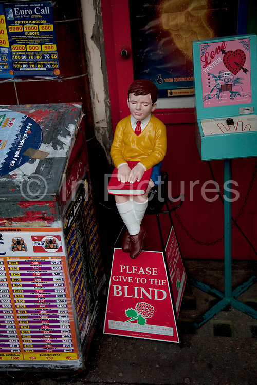 Old fashioned charity collection box depicting a little blind boy sitting with a book.