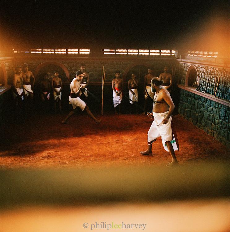 A martial arts teacher demonstrates to his class. Kerala, India