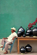 Artist with his black pots against green wall  Oaxaca, Mexico