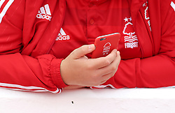 A Nottingham Forest fan holds a mobile phone in a Nottingham Forest phone case