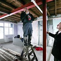 Nederland, Amsterdam , 7 december 2009..Peter Hildering (r) van de directieraad van woningbouwvereniging Eigen Haard bekijkt de renovatie werkzaamheden van de panden rond de Charlotte de Bourbonstraat..Foto:Jean-Pierre Jans