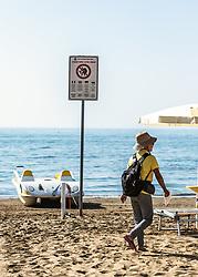 THEMENBILD - ein Schild am Strand, mit dem Hinweis, dass man sich strafbar macht, wenn man Dienste von Masseuren in Anspruch nimmt oder Produkte von Strandverkäufern kauft. Eine Masseurin geht auf dem Strand. Lignano ist ein beliebter Badeort an der italienischen Adria-Küste, aufgenommen am 16. Juni 2019, Lignano Sabbiadoro, Italien //  a sign on the beach indicating that you are liable to prosecution if you use the services of masseurs or buy products from beach vendors. A masseuse walks on the beach. Lignano is a popular seaside resort on the Italian Adriatic coast on 2019/06/16, Lignano Sabbiadoro, Italy. EXPA Pictures © 2019, PhotoCredit: EXPA/ Stefanie Oberhauser